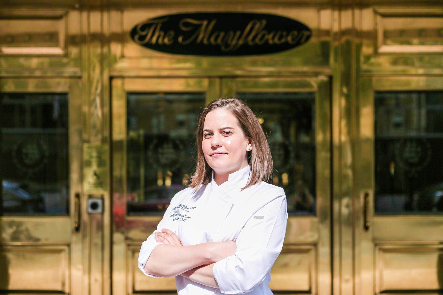 woman wearing white chef jacket standing in front of large copper doors